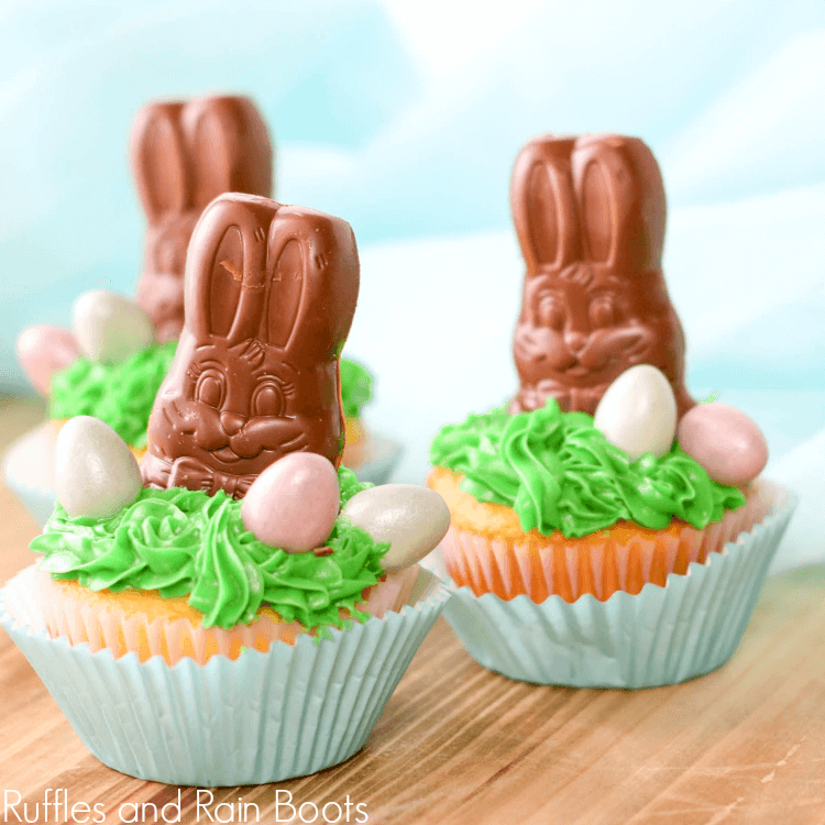 close up of three completed chocolate bunny cupcakes on wooden tabletop