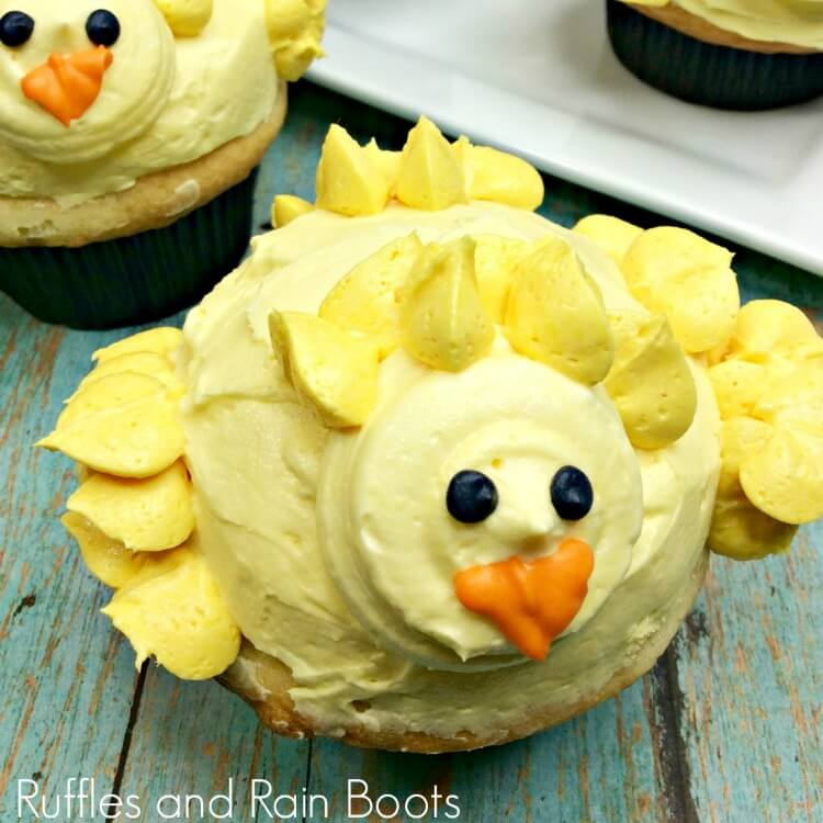 close up of chick cupcakes on green table