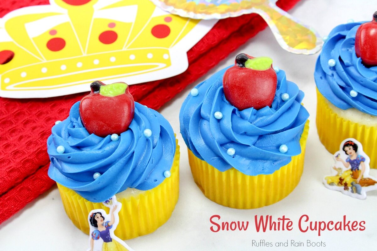 close up of three princess cupcakes on white and red background with text which reads Snow White Cupcakes