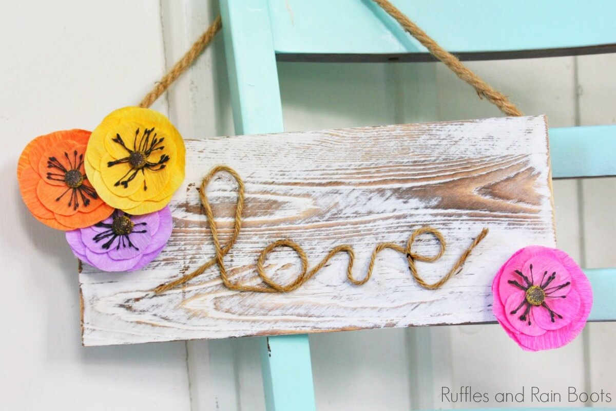 "farmhouse sign for spring which reads ""love"" hanging on the back of a blue chair"
