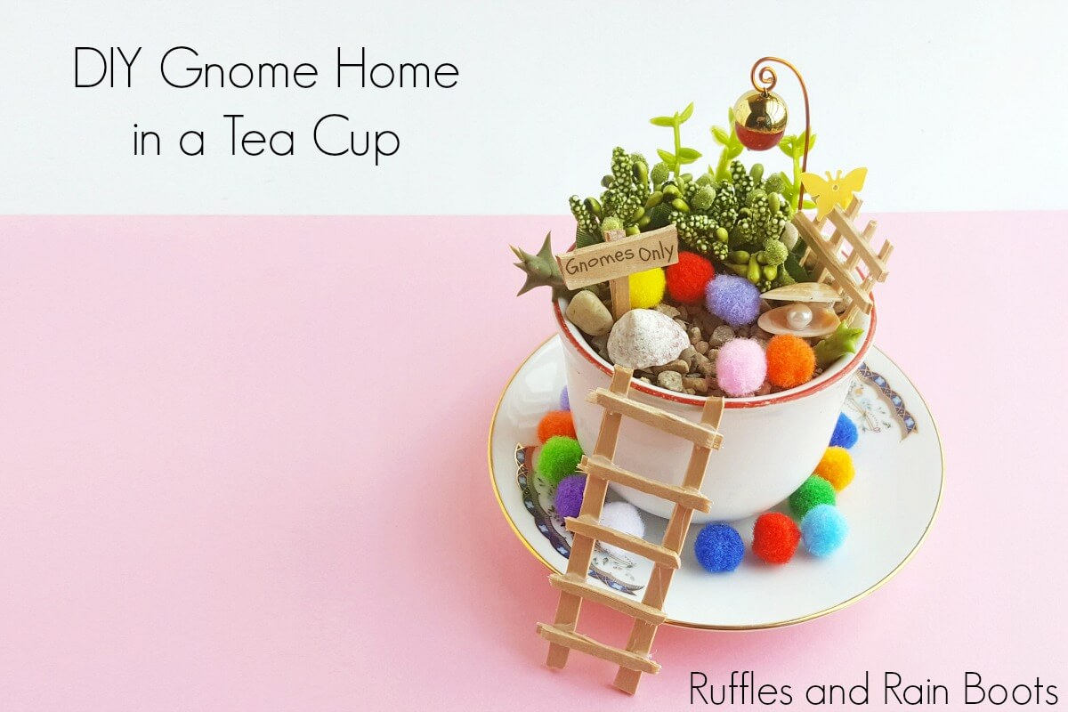 Gnome Teacup Garden with decorations and a ladder to get into the teacup on a pink background with text which reads gnome home in a tea cup