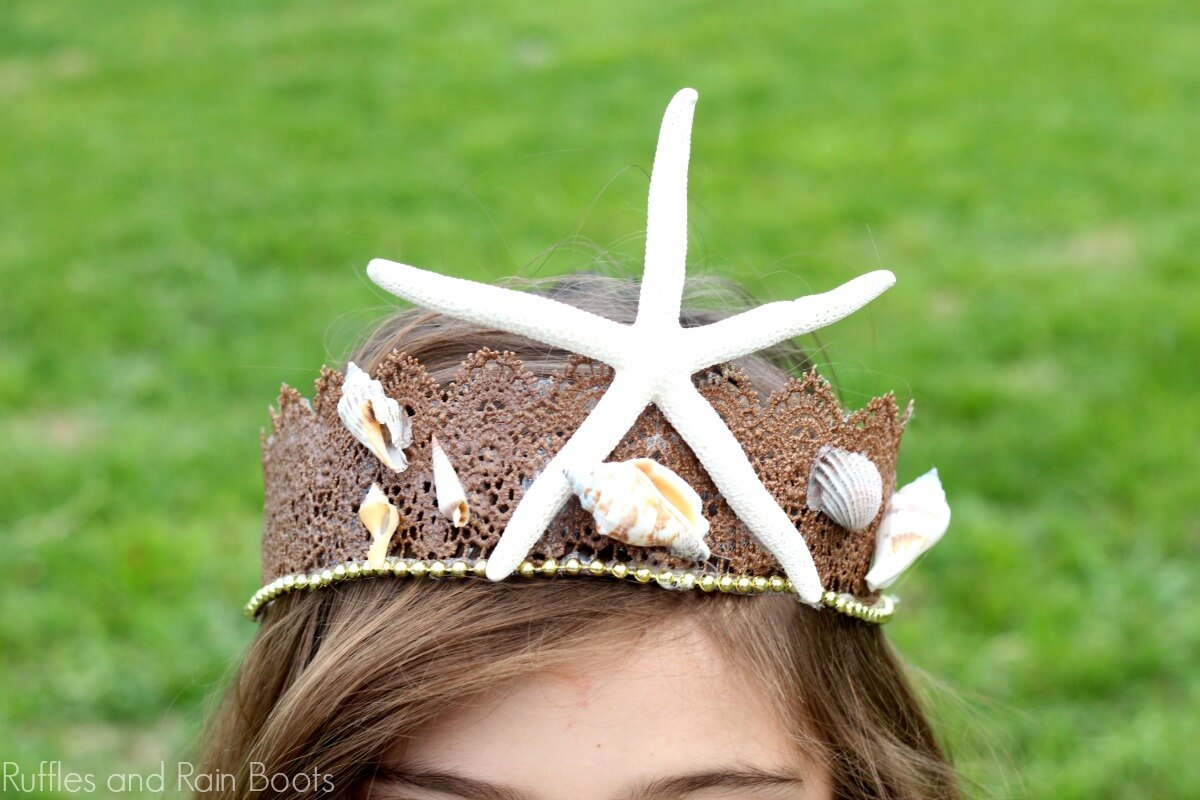 a little girl wearing a Mermaid Crown for Costumes or Dressup with a starfish and shells attached to it, while standing in a field of grass