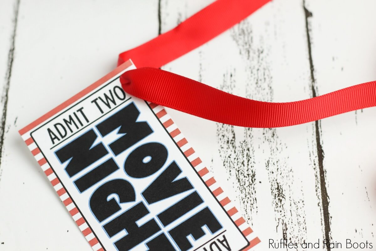 in process step of threading ribbon through free printable tag which reads movie night admit two on a white background