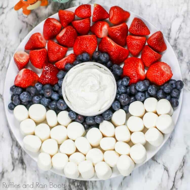 overhead view of strawberries, bananas, blueberries and dip arranged on a tray to look like a pokemon pokeball fruit tray
