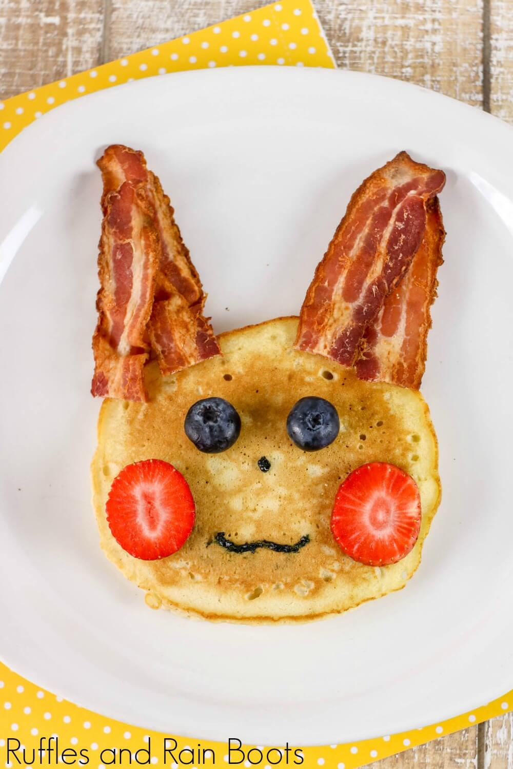 "pancake with bacon ""ears"", strawberry ""cheeks"", blueberry ""eyes"", and icing for a nose and mouth made to depict a pikachu pokemon pancake on a plate"