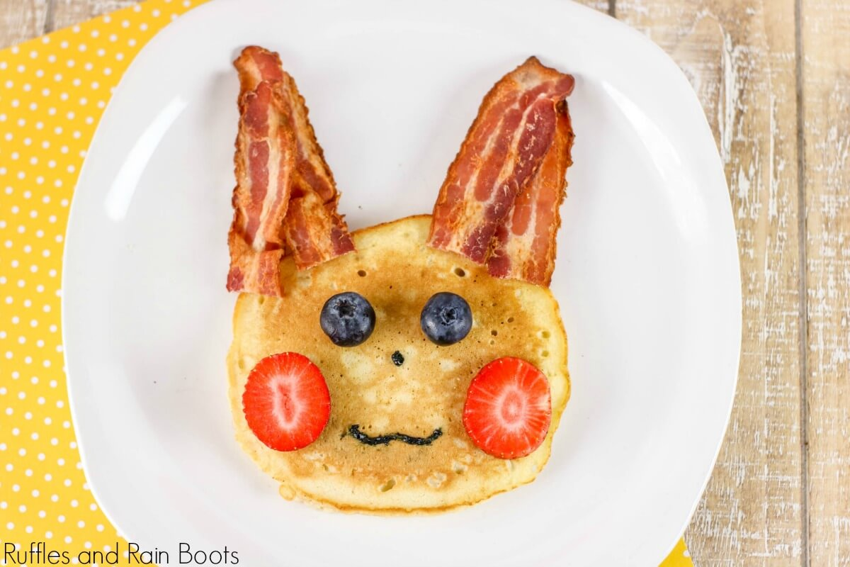 "pancake with bacon ""ears"", strawberry ""cheeks"", blueberry ""eyes"", and icing for a nose and mouth made to depict pikachu pancake for a pokemon breakfast on a white plate"