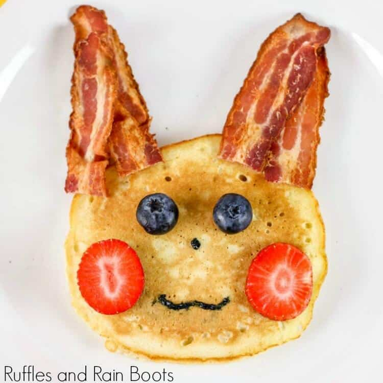 "pancake with bacon ""ears"", strawberry ""cheeks"", blueberry ""eyes"", and icing for a nose and mouth made to depict a pikachu from pokemon on a white plate"