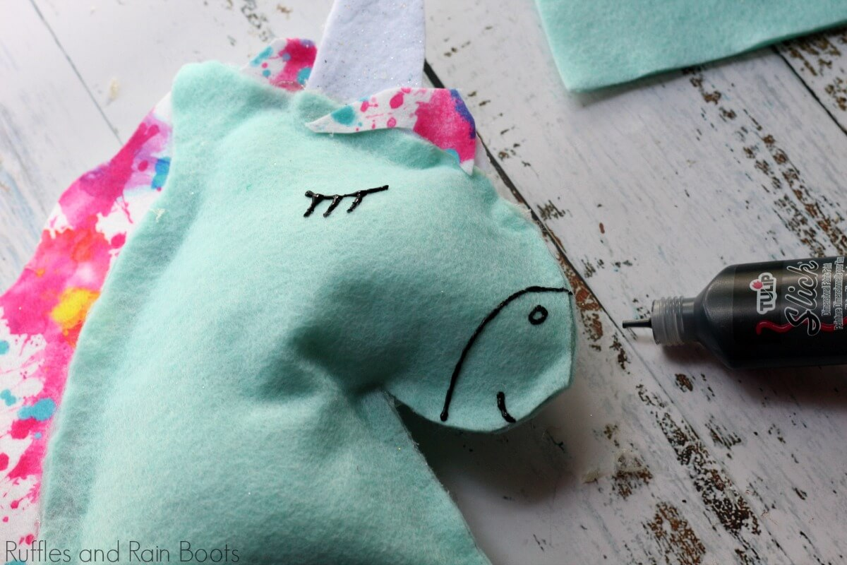 adding eyes to the unicorn pillow with puffy paint