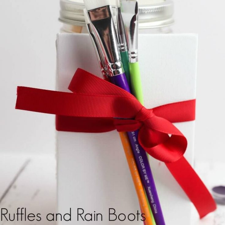paint brushes tied to a jar with a canvas to represent the paint date night in a jar craft