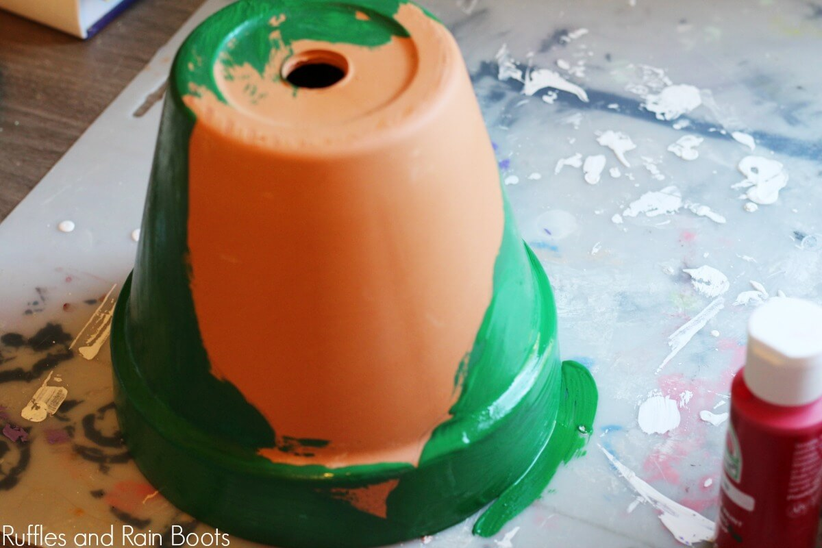 paint gnome on clay pot on grey background