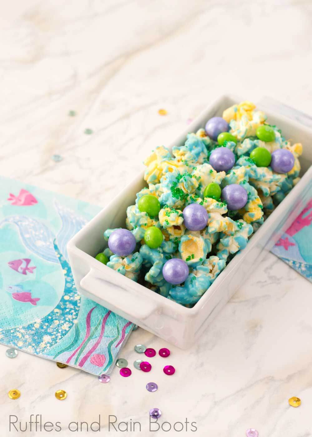 easy candy popcorn recipe candy mermaid popcorn in a rectangle bowl on a white background
