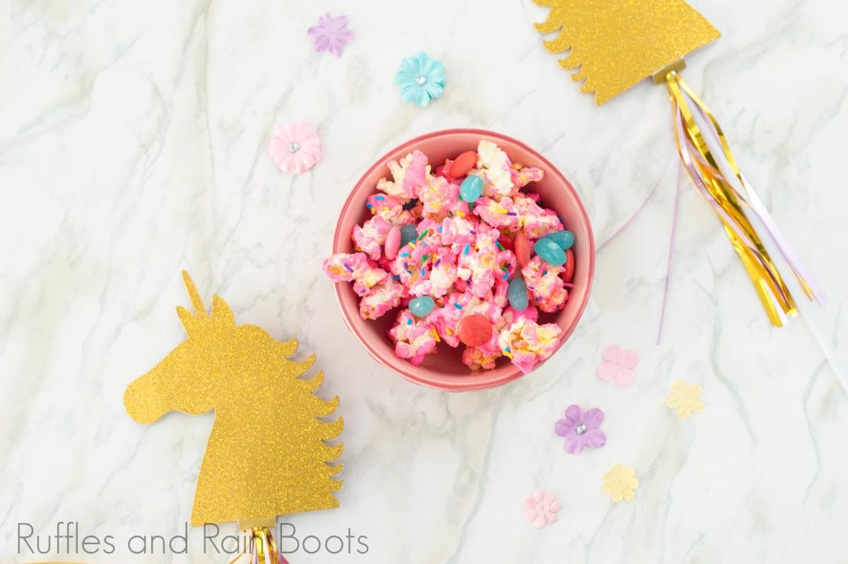 overhead view of sweet candied unicorn popcorn recipe in a pink bowl on a white background