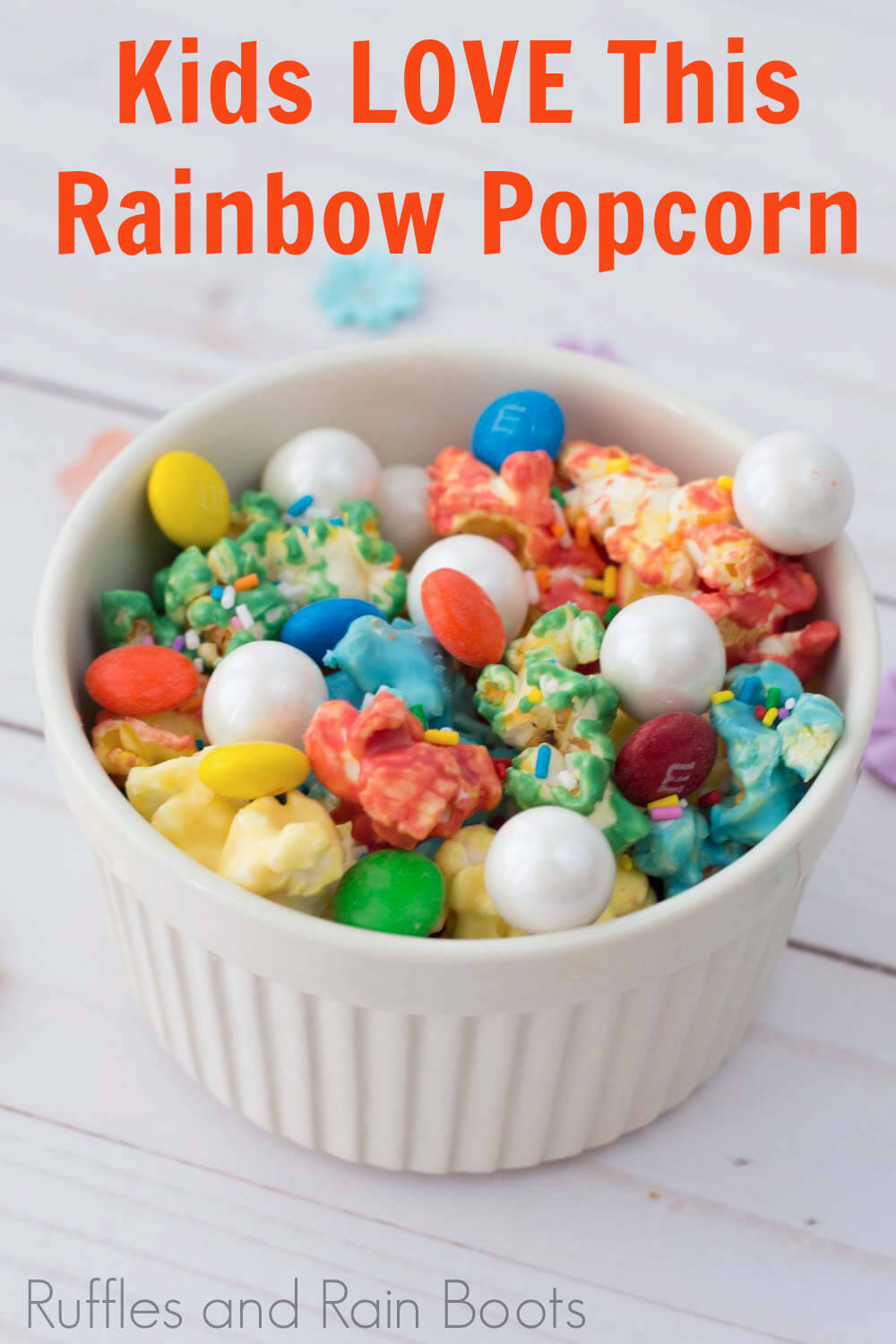 easy candy popcorn recipe for multi-colored popcorn in a white bowl with text which reads kids love this rainbow popcorn