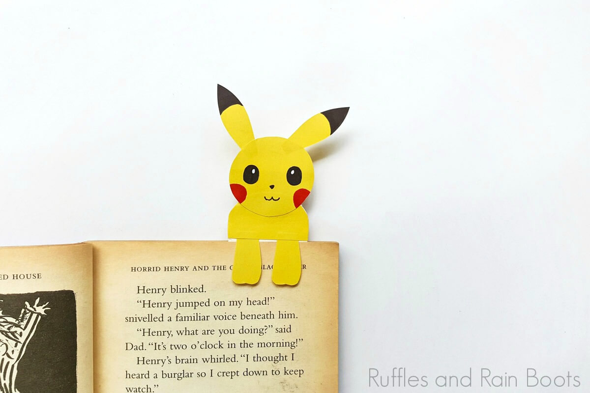 pikachu bookmark hug style on a book on a white background