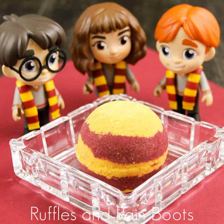 griffindor bath bombs in a clear dish with harry potter movie figurines on a red background