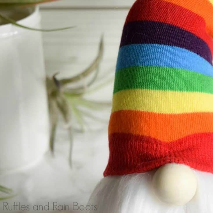 close up of nordic gnome with a twisty hat on white marble background with air plants