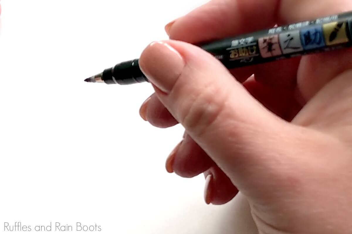close up of how to hold a brush pen for lettering