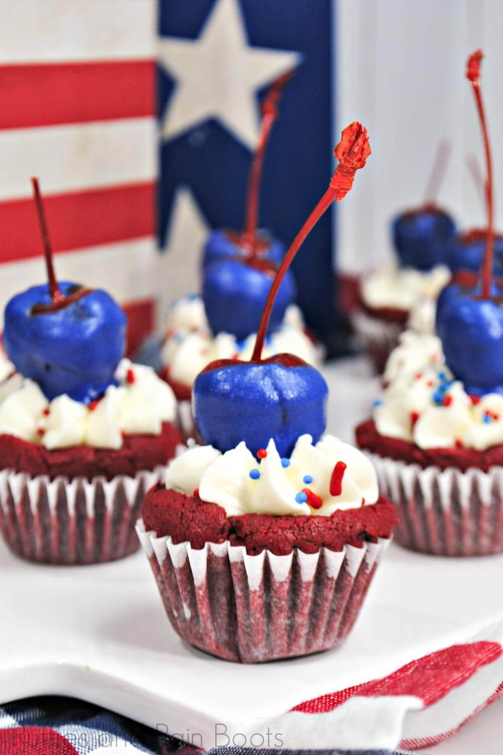 side view of several red velvet brownie bites, red brownie mini-cupcakes with white icing topped with blue-chocolate covered cherry on top on a white plate with a flag background