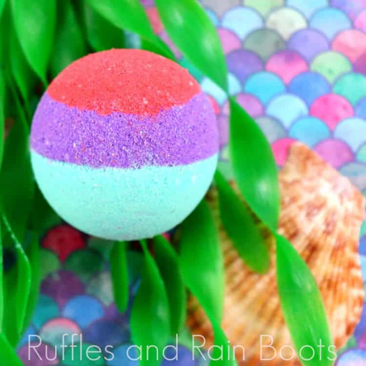 single red purple and teal disney princess ariel bath bombs on fake sea grass with a shell sitting on a brightly colored scale-design table
