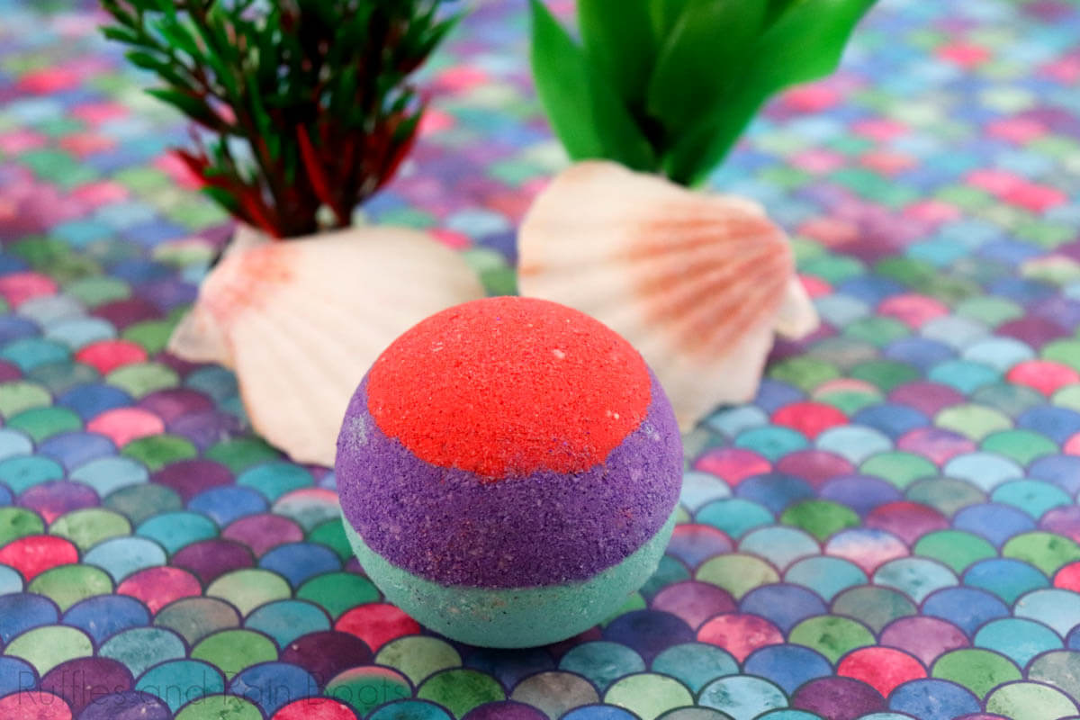 red purple and teal bath bomb for an easy little mermaid gift ideas on a colorful shell table with shells and fake sea grass in the background