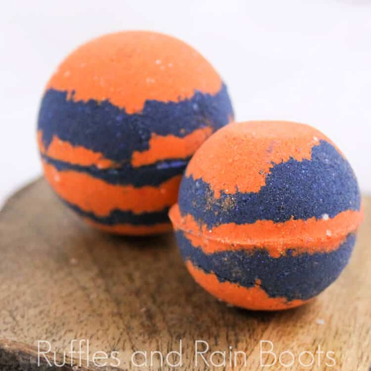 two bright orange and blue princess merida bath bombs on a wood table on a white background