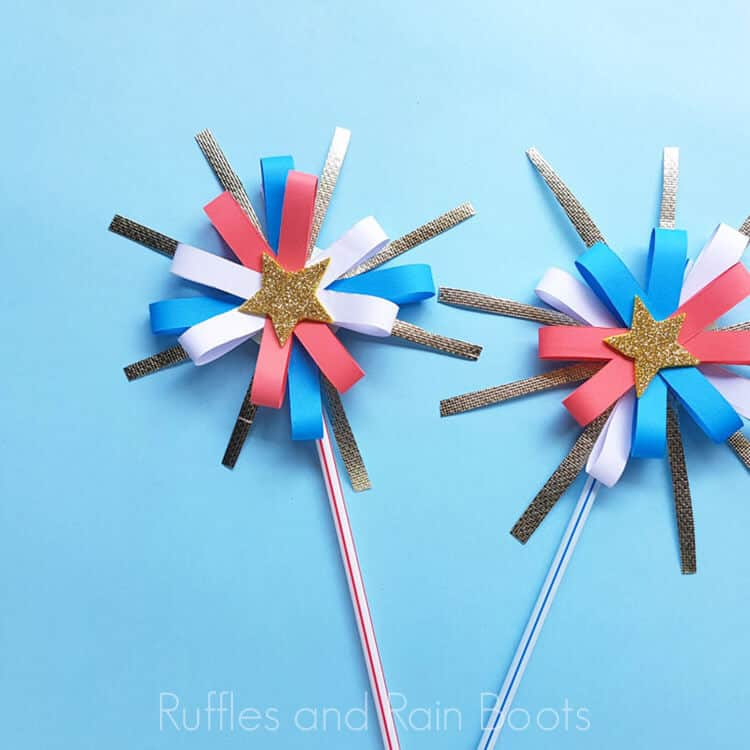 two paper fireworks craft for kids on a blue background