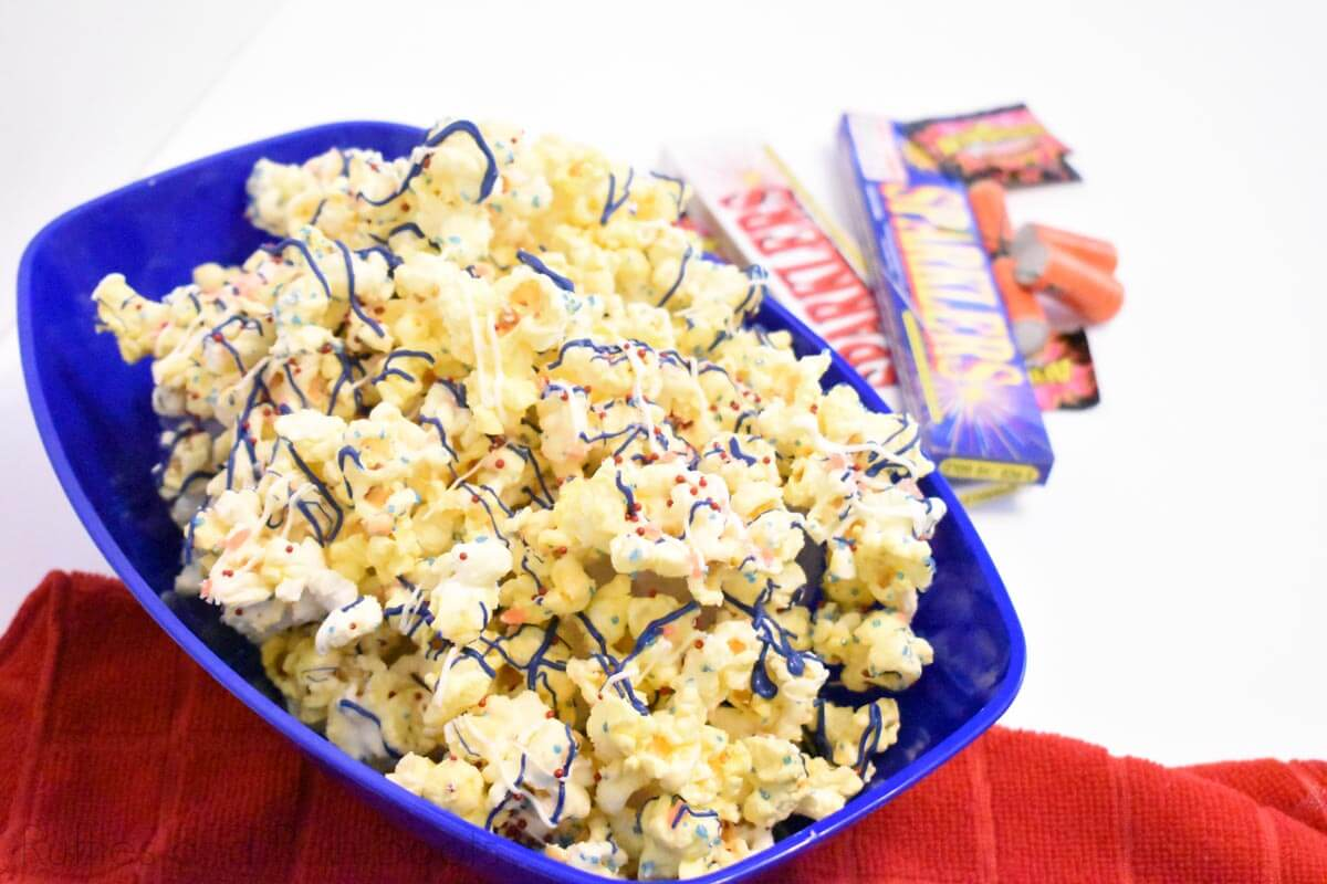 july 4th popcorn with red white and blue candy and pop rocks on white table with firecrackers