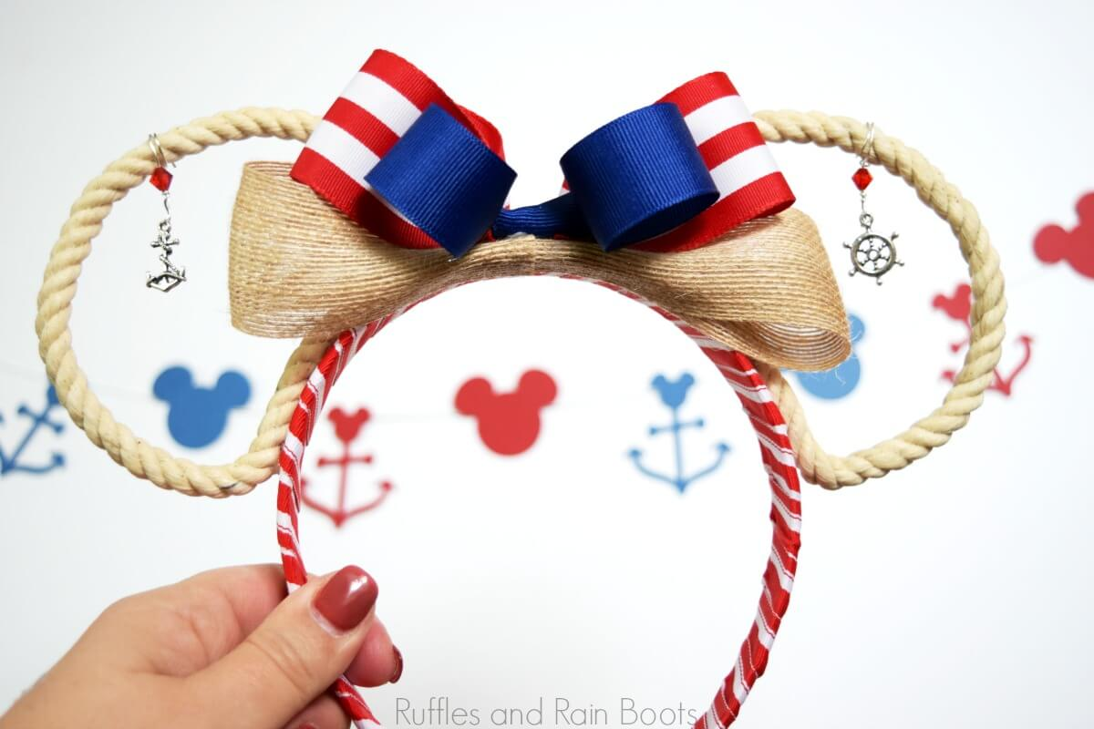 hand holding adorable Disney cruise ears with open rope ears and nautical charms on white background