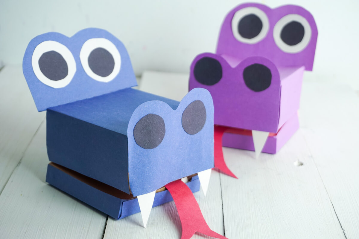 purple and blue examples of how to make a paper dragon puppet on a white wood background