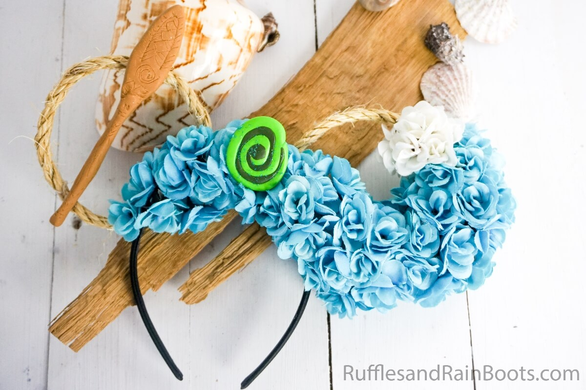 easy diy moana mickey ears for disney on a white wood background with driftwood and shells
