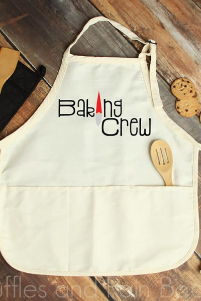 free baking crew svg for christmas apron placed on wood background with kitchen utensils and chocolate chip cookies