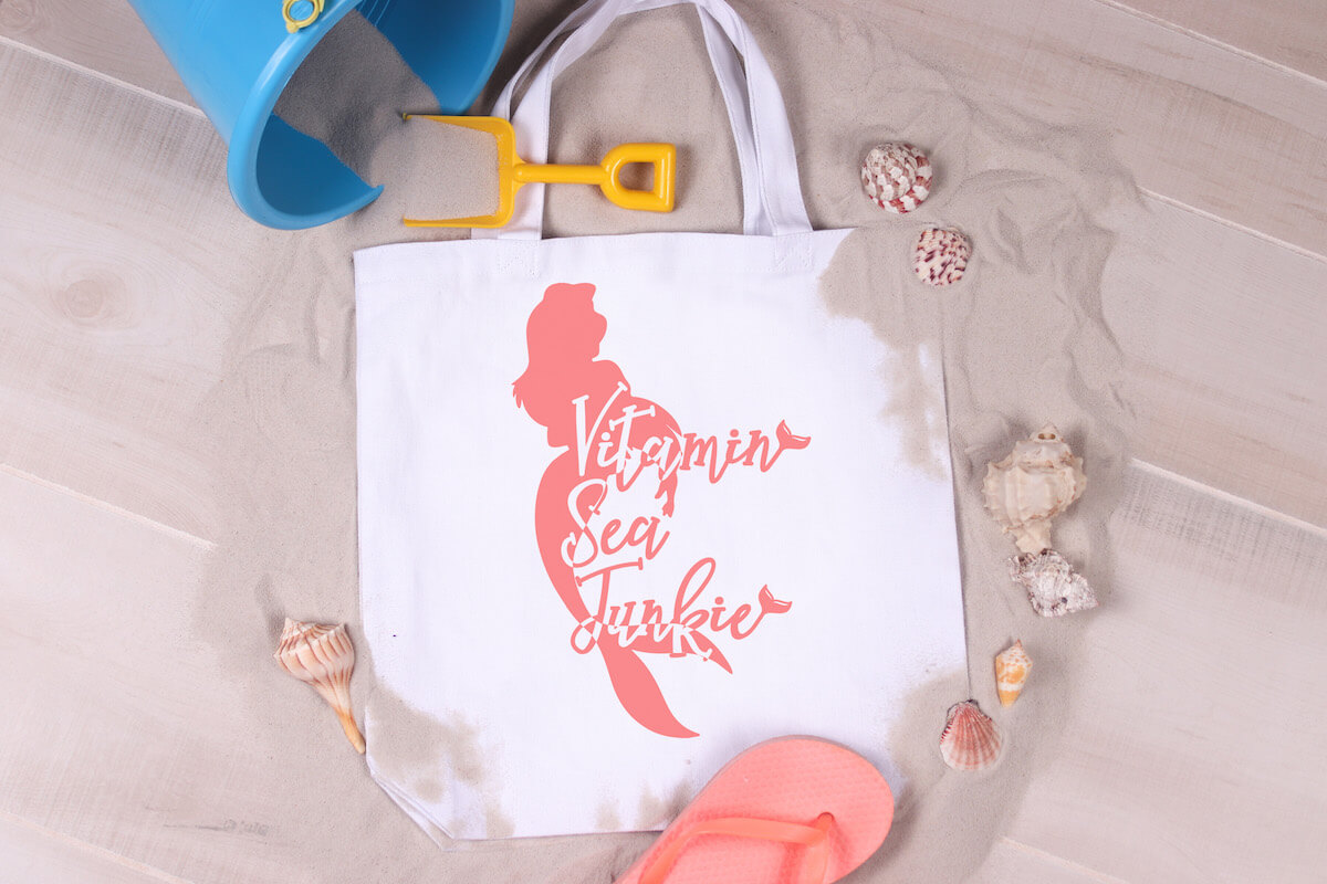 Vitamin Sea Junkie mermaid svg file on a beach bag on a background of sand surrounded by shells, flip flops and a kid's toy bucket and shovel