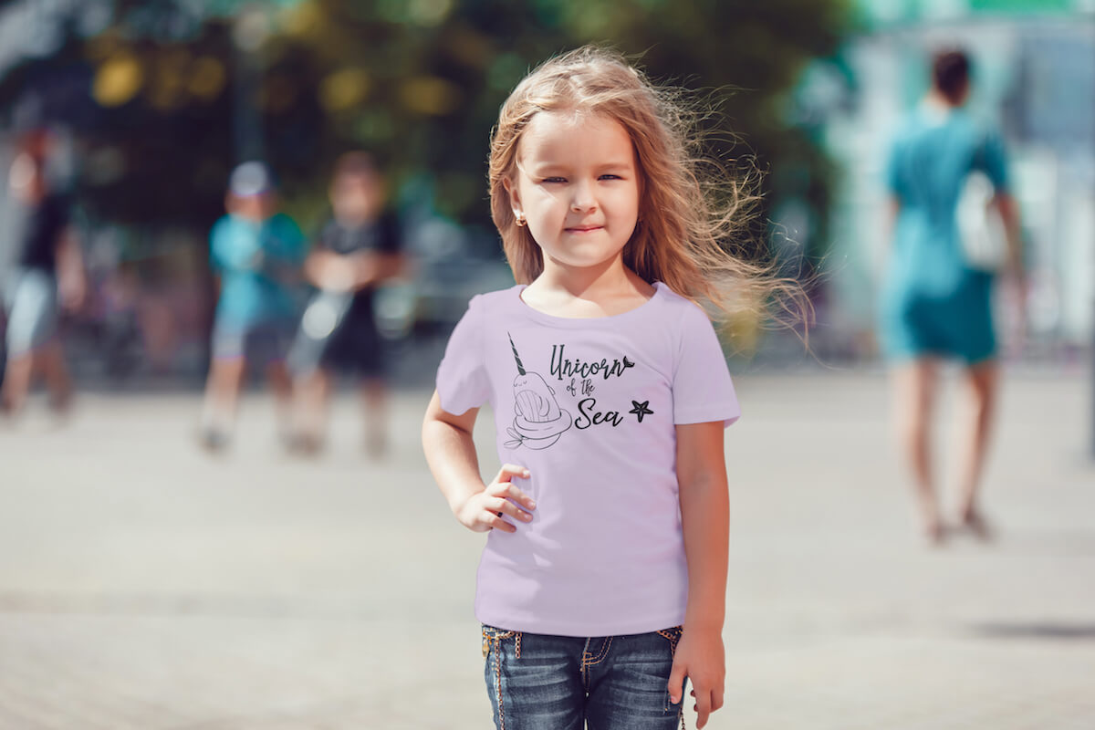 unicorn of the sea mermaid svg on a shirt worn by a little girl in front of a blurred, crowded street