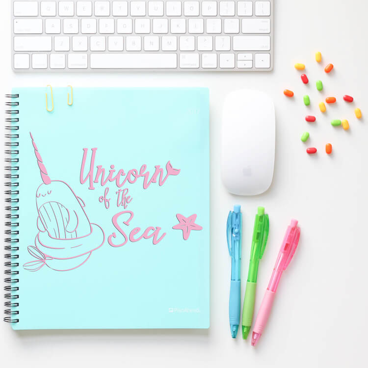 free Unicorn of the Sea cut file for cricut on notebook on a white desk with pens, a mouse, keyboard and thumbtacks