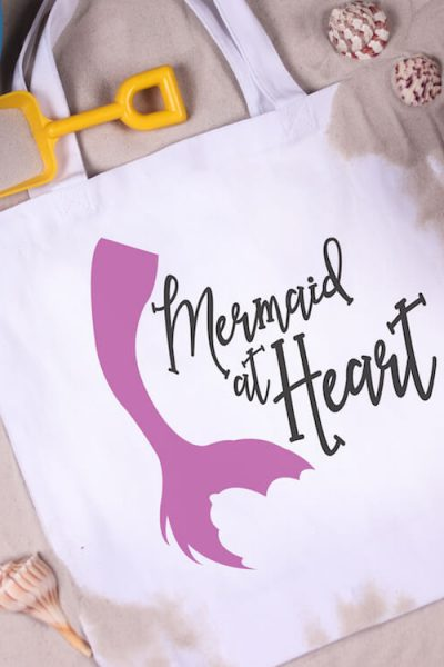 mermaid at heart free mermaid svg for silhouette on a beach bag laying in a bed of sand with kid's beach toys and sea shells scattered around