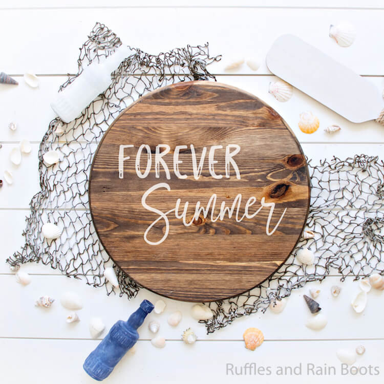 Forever Summer free summer cut file for Cricut Wood Round Sign on a fishing net with sea shells scattered around with an oar and bottle on a white background