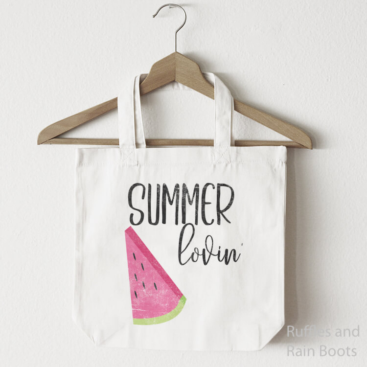 Summer Lovin' free summer cut file for SIlhouette with Watermelon Slice on a canvas bag hanging from a wooden clothes hanger on a white background