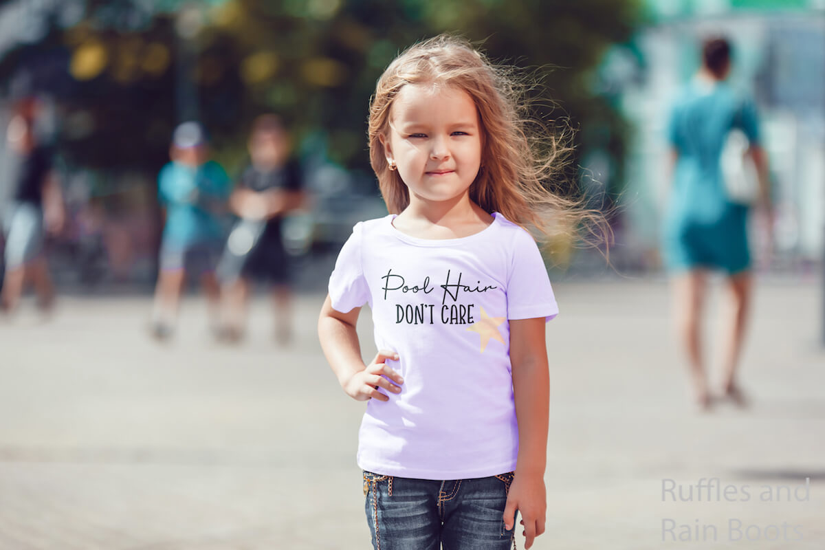 Pool Hair Don't Care with Starfish summer SVG on Kid T-Shirt which a little girl is wearing while standing on a street with people in the background