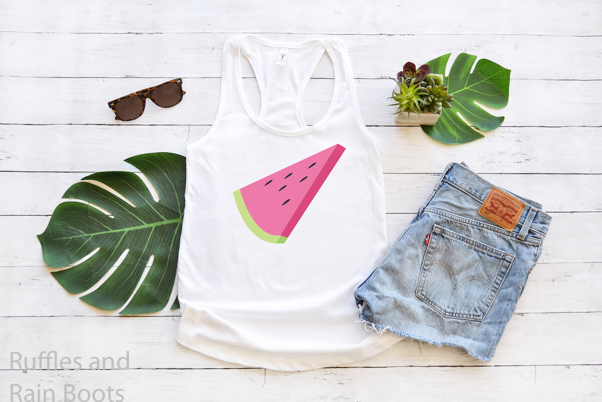 Watermelon Slice free summer svg for Cricut on Tank Top next to jean shorts and palm leaves on a white wood background