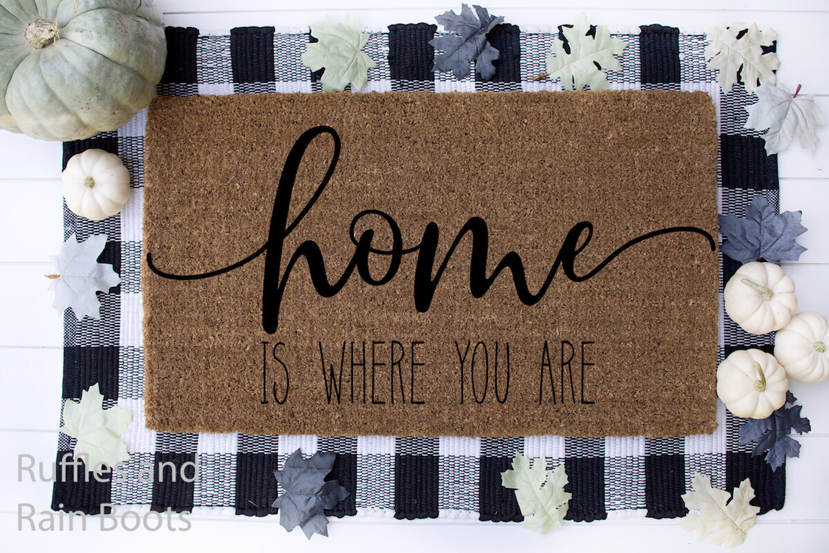 home is where you are Farmhouse SVG for cutting machines on doormat on a buffalo check mat on a white wood background