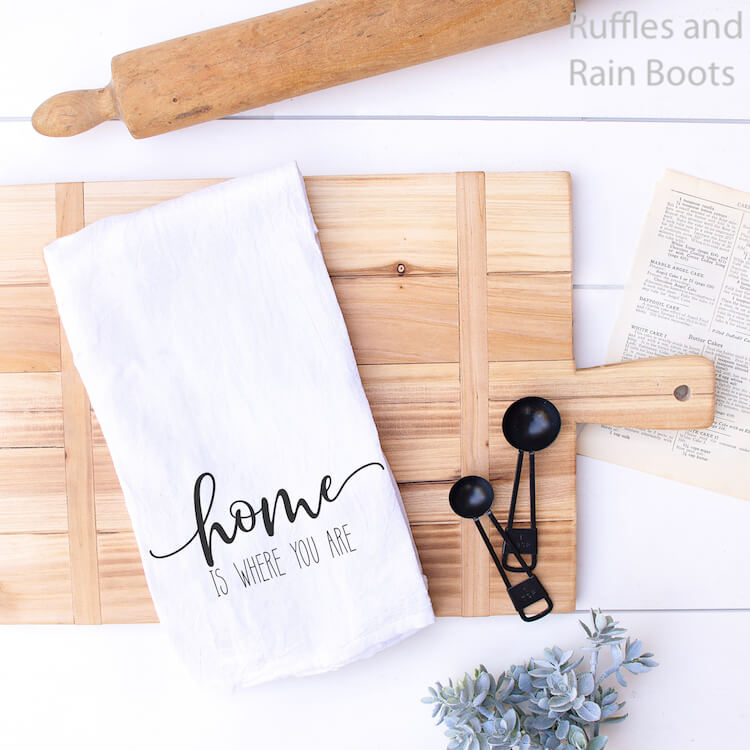 home is where you are farmhouse SVG on towel on a cutting board with some measuring cups and a rolling pin on a white wood background