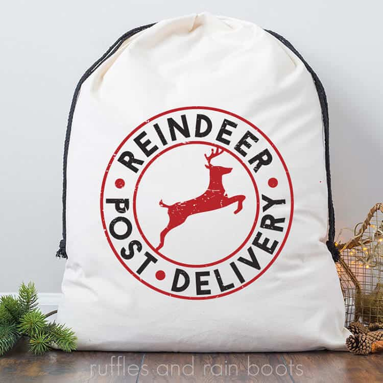 handmade Santa sack gift bag with free Reindeer Delivery Christmas SVG leaning up against the wall next to a Christmas tree