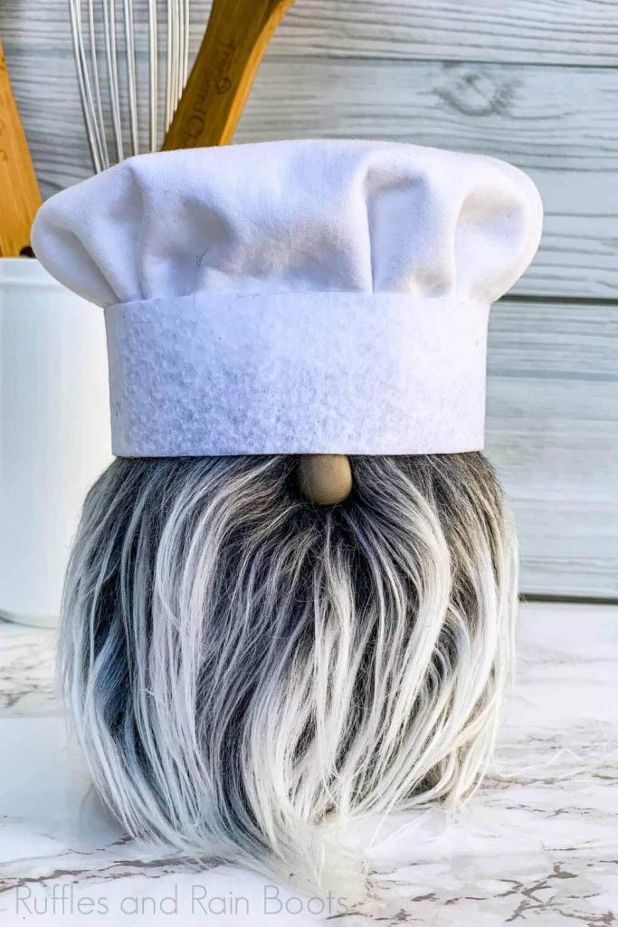 close up of chef gnome with chef toque, gray mongolian fur beard, and polymer clay nose on white wood and marble background with baking utensils