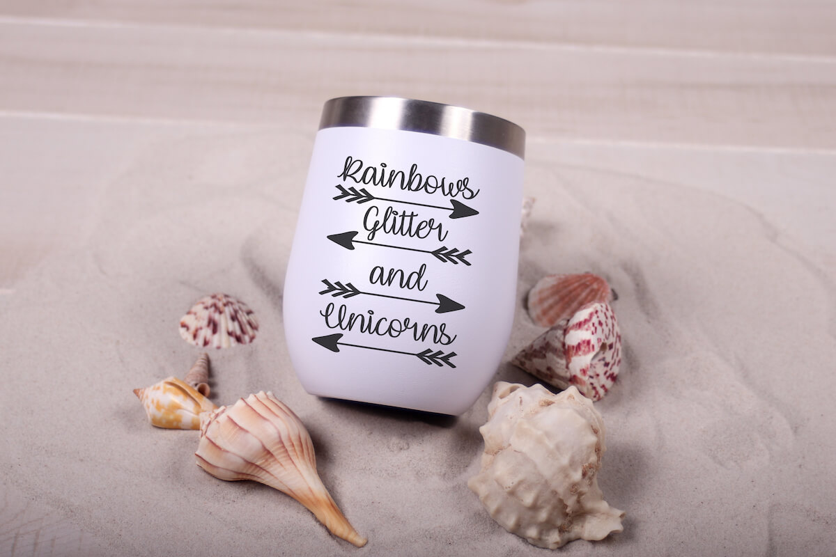Rainbows Glitter and Unicorns svg on travel mug on a bed of sand with sea shells piled around