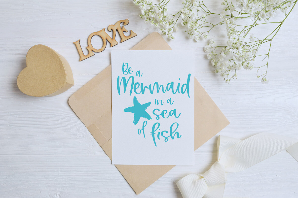 Be a Mermaid in a Sea of Fish free mermaid cut file for silhouette on paper sign with other desk-type items scattered around