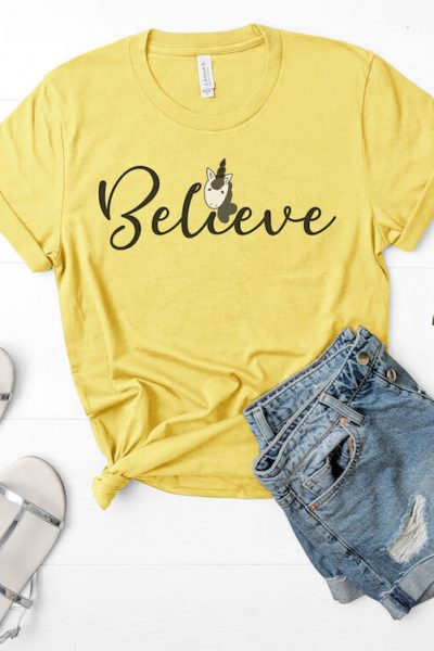 Believe free unicorn svg on yellow t-shirt with jean shorts, sandals and sunglasses on white background