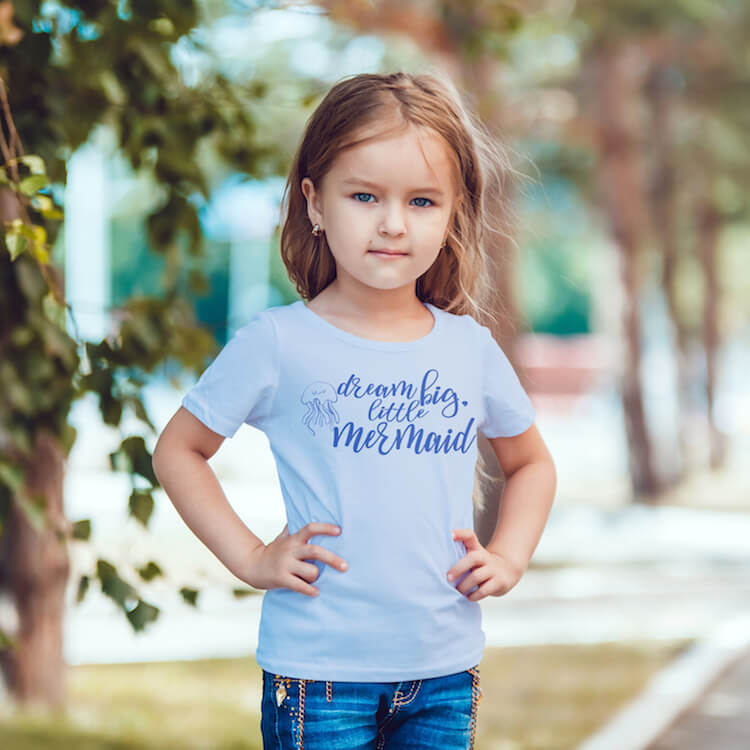 Dream big little Mermaid free mermaid cut file for cutting machines on kid shirt worn by a little girl standing on the street with trees in the background