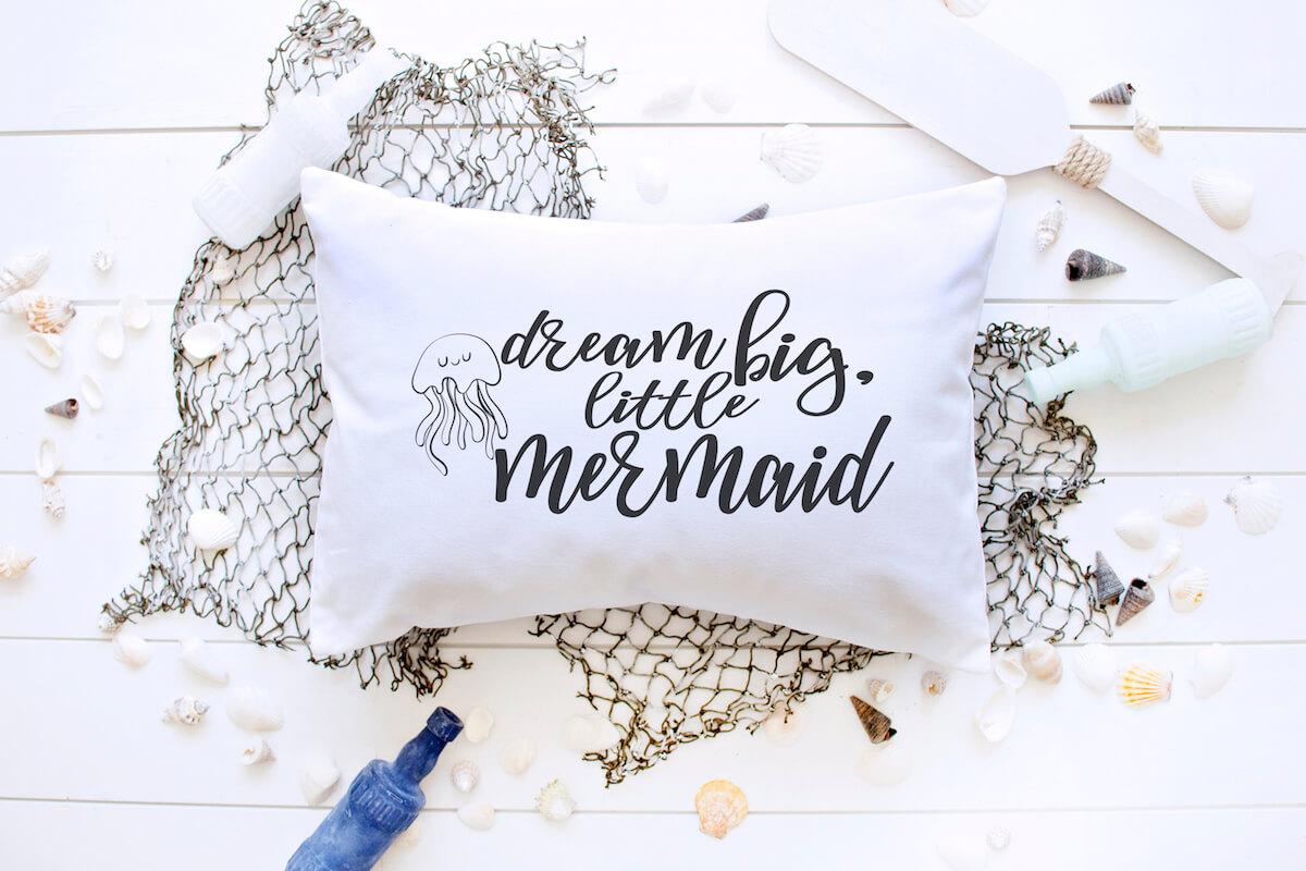 Dream big little Mermaid free mermaid svg on a throw pillow on a fishing net with oar and blue bottle on a white wood background