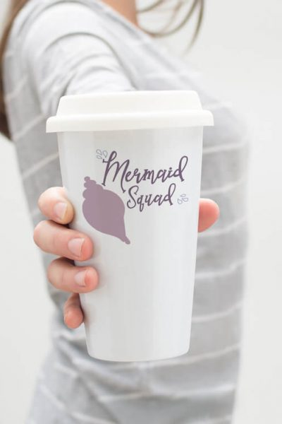 Mermaid Squad free mermaid file for cutting machines on travel cup held by a lady in a grey shirt on a white background