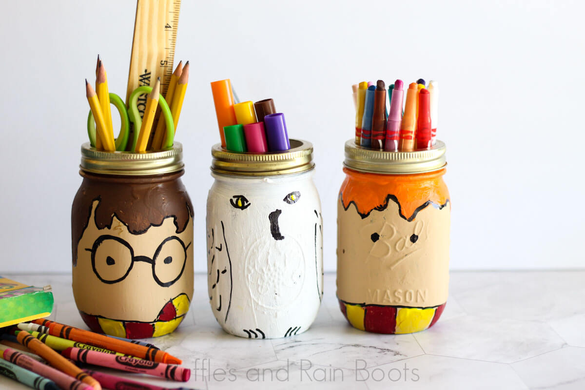 painted Harry Potter mason jars on marble background which features Harry Potter Ron Weasley and Hedwig the owl